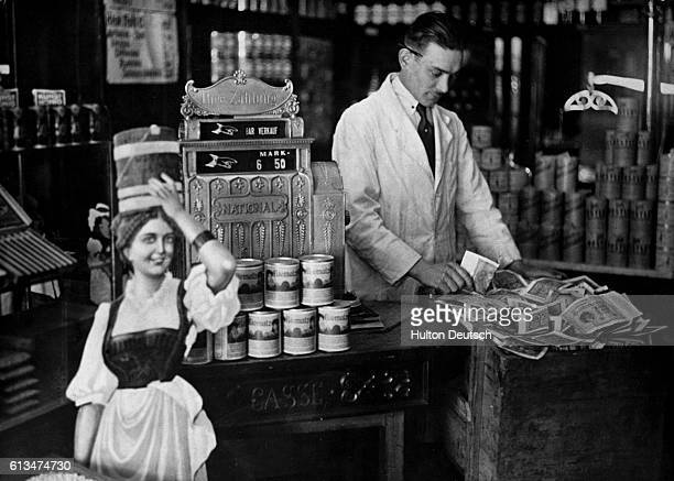 As a result of inflation in Weimar Germany a grocer's cash register which was formerly rarely full has to be regularly emptied and its contents...