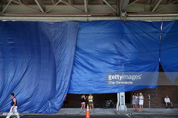 As a safety precaution a curtain of blue plastic tarps hangs front the underside of the Whitehurst Freeway overpass to shield the location of...