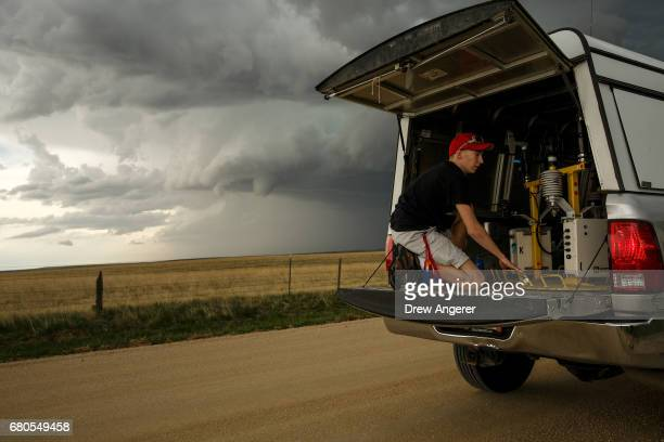 As a small funnel cloud develops behind him Hunter Anderson a meteorology student at St Cloud State University and current intern with the Center For...