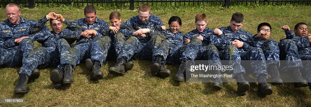 """As a team these midshipmen perform abdominal crunches during sea trials at the United States Naval Academy in Annapolis, Maryland on May 14, 2013. Sea Trials is modeled after the Marine Corps' Crucible and the Navy's Battle Stations recruit programs. It is a """"capstone"""" event for the fourth class midshipmen (freshmen or """"plebes"""") and serves as a leadership challenge for the upper class. Sea Trials is led by academy upper class and provides a final physical and mental challenge to the plebes, designed to test their teamwork and to reinforce their bonds as a company and class. Plebes are physically and mentally tested through a variety of challenges in different stations located across the Academy and Naval Support Activity Annapolis. At the end of Sea Trials, the company of plebes who demonstrated the top unit performance through endurance and spirit during the entire course will be recognized with the """"Iron Company"""" award during a brief presentation."""