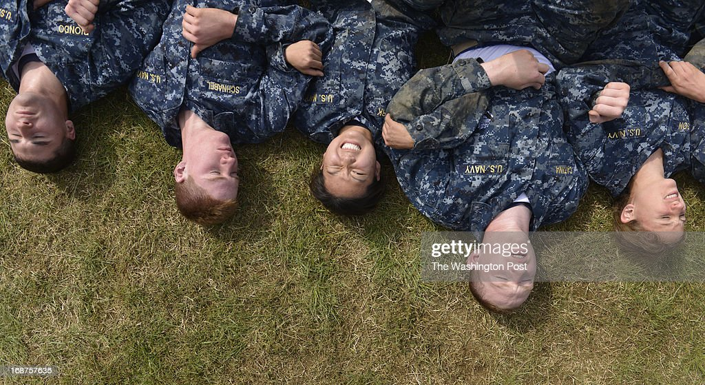 "As a team these midshipmen perform abdominal crunches during sea trials at the United States Naval Academy in Annapolis, Maryland on May 14, 2013. Sea Trials is modeled after the Marine Corps' Crucible and the Navy's Battle Stations recruit programs. It is a ""capstone"" event for the fourth class midshipmen (freshmen or ""plebes"") and serves as a leadership challenge for the upper class. Sea Trials is led by academy upper class and provides a final physical and mental challenge to the plebes, designed to test their teamwork and to reinforce their bonds as a company and class. Plebes are physically and mentally tested through a variety of challenges in different stations located across the Academy and Naval Support Activity Annapolis. At the end of Sea Trials, the company of plebes who demonstrated the top unit performance through endurance and spirit during the entire course will be recognized with the ""Iron Company"" award during a brief presentation."