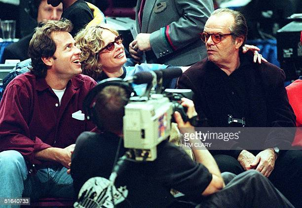 As a television cameraman focuses on actor Jack Nicholson his girlfriend Rebecca Broussard and actor Greg Kinnear look at his image on the overhead...