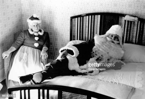 As a woman dressed as Mrs Claus looks on a man dressed as Santa Claus reclines across a bed Albion New York 1964