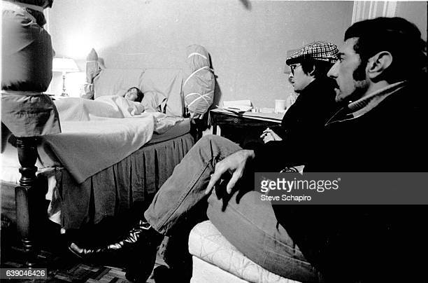 As American actress Linda Blair lies on a bed in the background film director William Friedkin and author screenwriter William Peter Blatty sit...