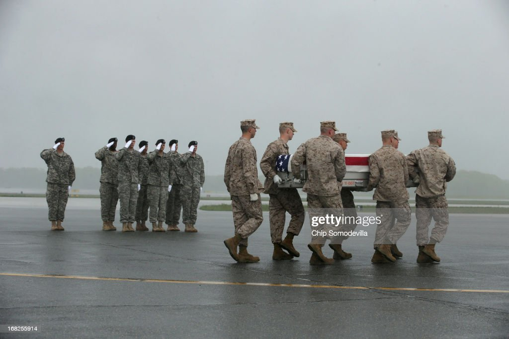 As an Army carry team salutes, a U.S. Marine Corps carry team carries the flag-draped transfer case with the remains of Marine Staff Sgt. Eric Christian of Warwick, New York across the tarmac in the pouring rain at Dover Air Force Base May 7, 2013 in Dover, Delaware. Assigned to 2nd Marine Special Operations Battalion out of Camp Lejeune, North Carolina, Christian and one other Marine died May 4, while conducting combat operations in Farah province, Afghanistan.