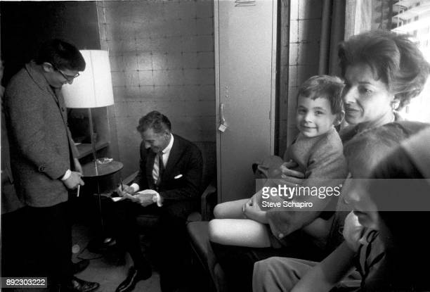 As an unidentified man watches American composer musician and conductor Leonard Bernstein signs an autograph backstage at Carnegie Hall New York New...