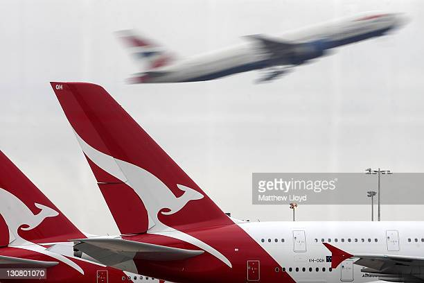 As another airline's plane takes off Qantas airline jets sit grounded on the tarmac at Heathrow airport on October 30 2011 in London England Qantas'...