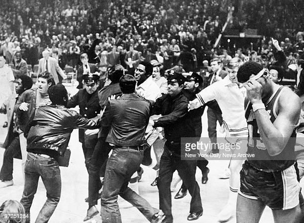 As berserk fans cascade onto floor police surround Knicks' Willis Reed after the New Yorkers topped the Los Angeles Lakers at the Garden winning...