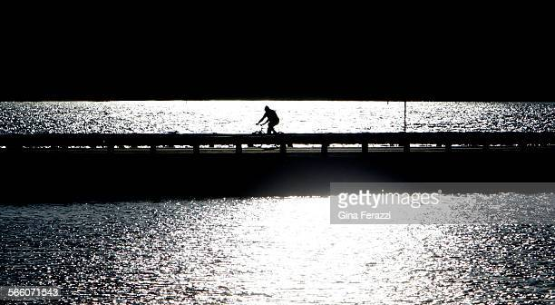 As Big Bear Lake glistens from a sunset a lone cyclists rides across the bridge on Stanfield Cutoff By Friday afternoon the bridge will be buzzing...