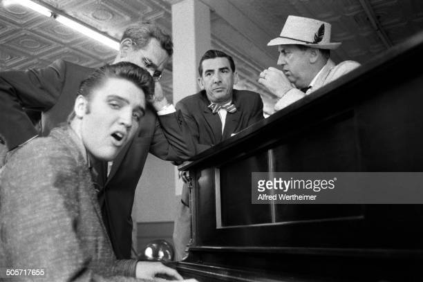 Alfred Wertheimer/Getty Images As Colonel Tom Parker and several unidentified television executives listen American musician Elvis Presley plays...