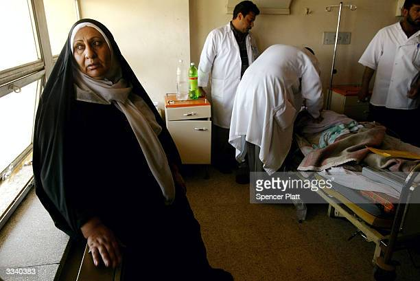 As doctors work on Fadhila Nuseif a wounded pregnant woman from the besieged town of Fallujah her aunt looks out a window April 11 2004 in Baghdad...