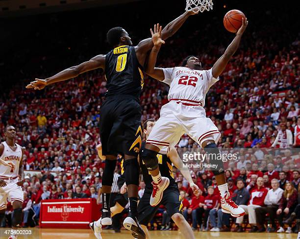As Gabriel Olaseni of the Iowa Hawkeyes defends Stanford Robinson of the Indiana Hoosiers shoots the ball under the basket at Assembly Hall on...