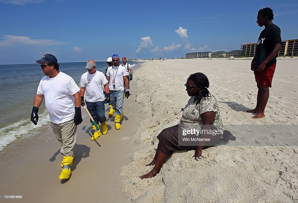 As Gwen Benjamin and Shun Benjamin watch, contract workers patrol the beach to pick up oil that washed ashore on a public beach on June 2, 2010 in Dauphin Island, Alabama. Oil believed to be from the Deepwater Horizon oil rig accident began to appear yesterday on the shores of Alabama.