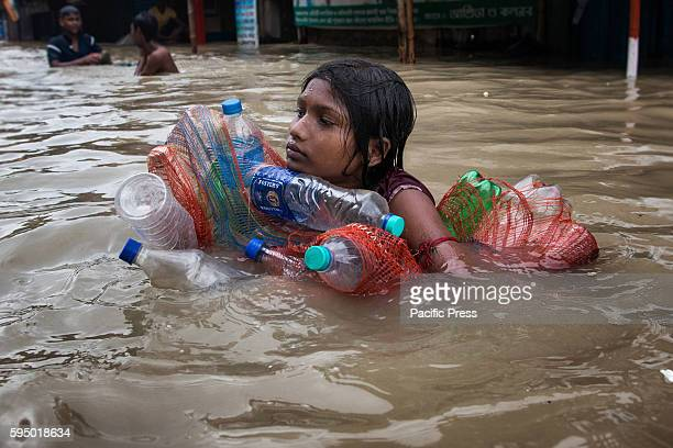 As heavy rainfall and rising river Ganges water level flooded Kalighat area of Kolkata city a little girl wades through flooded water with empty...