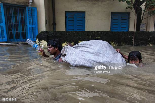 As heavy rainfall and rising river Ganges water level flooded Kalighat area of Kolkata city a rag picker wades through neck deep water with her...