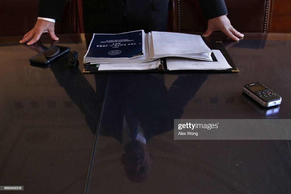 As his reflection is seen on a piece of table-top glass, Chairman of House Ways and Means Committee Rep. Kevin Brady (R-TX) speaks during a news briefing on the tax reform legislation November 2, 2017 on Capitol Hill in Washington, DC. House Republicans will unveil the tax reform legislation today.