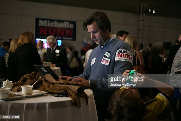 As his son Oscar GarciaIde finishes a can of soda Humberto GarciaSjogrim checks election results data during the election party for Georgia...