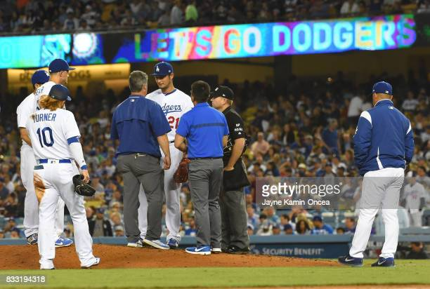 As manager Dave Roberts of the Los Angeles Dodgers waits to the side team trainers talk to Yu Darvish of the Los Angeles Dodgers at the start of the...