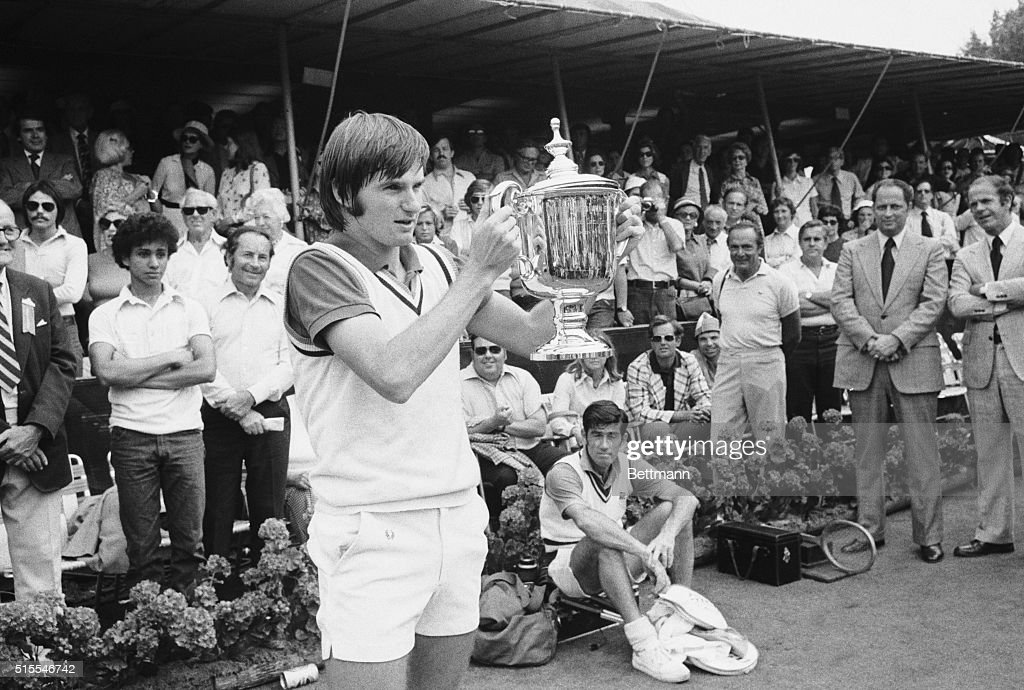 As men's singles victor Jimmy Connors holds up the trophy, Ken Rosewall, whom he defeated, looks on at lower right at the U.S. Open tennis tourney at New York's Forest Hills September 9. Connors won 6-1, 6-0, 6-1.