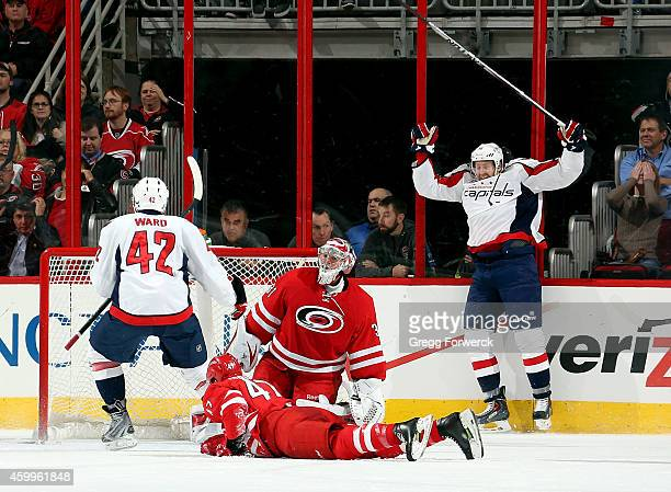 As Michal Jordan of the Carolina Hurricanes lifts himself from the ice and Anton Khudobin looks on Joel Ward and Eric Fehr of the Washington Capitals...
