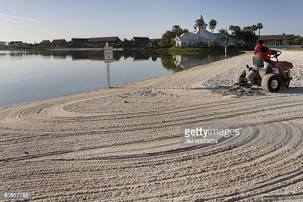As morning arrives groundsmen rake the beaches of Disney's Grand Floridian Resort Spa at Disney World in Orlando Florida April 11 2008 The complex is...