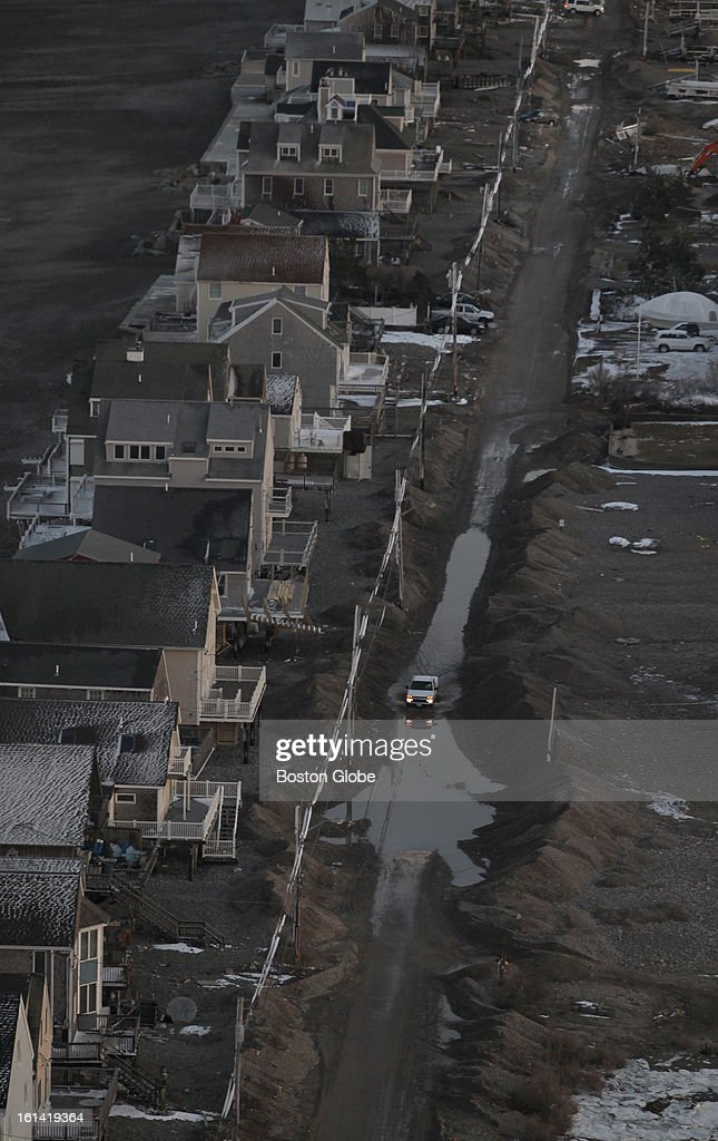 As night sets in, there is still no power in Humarock, Mass., as a vehicle makes its way through a flooded street with mounds of sand on both sides of the roadway after a blizzard hit New England.