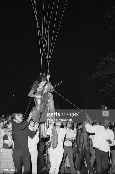 As part of the Annual New York Avant Garde Festival American cellist and performance artist Charlotte Moorman hangs suspended from heliumfilled...