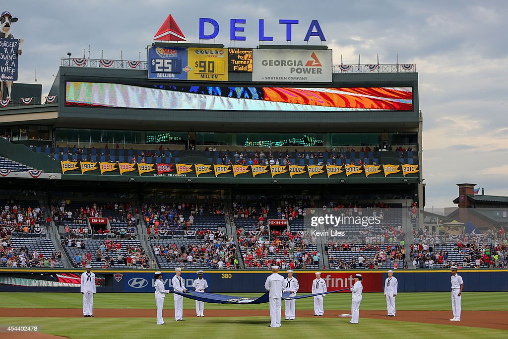 As part of the Atlanta Braves' United States Navy Celebration, members of the U.S. Navy holds their service flag during the national anthem prior to the game between the Atlanta Braves and Miami Marlins at Turner Field on August 30, 2014 in Atlanta, Georgia.