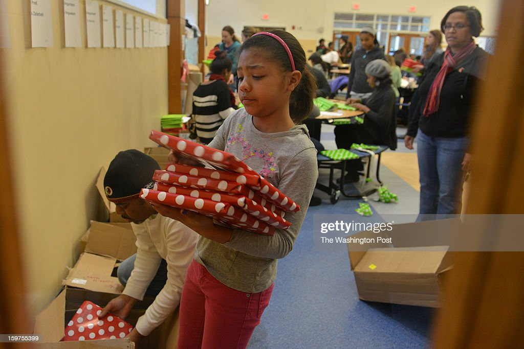 As part of the National Day of Service, Robin Barbour, 9, of Ashburn, VA, helps her father, Paul Barbour, L, package gift-wrapped books as volunteers from the region and those coming into DC for the Obama inauguration, inscribe and gift-wrap books for needy DCPS (DC Public School) children at Turner Elementary School on Saturday, January 19, 2012, in Washington, DC.
