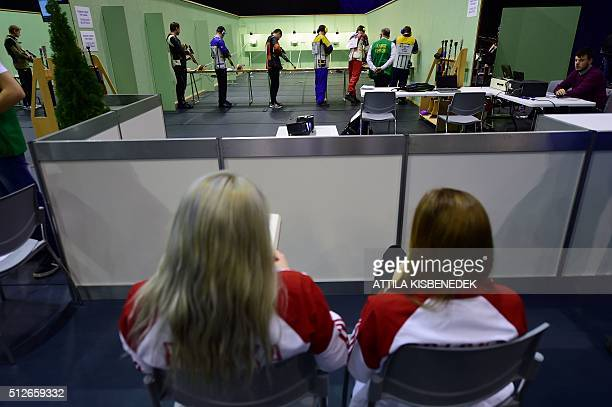 As Polish team members look at competitors shoot in the test range of running target category in AUDI Arena of Gyor on February 26 2016 prior to...