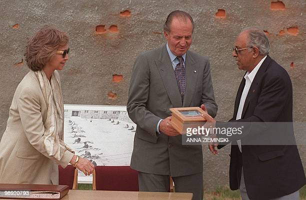 As Queen Sofia of Spain watches Ahmed Kathrada of the President's Office presents Spanish King Juan Carlos with a gift of a stone from the lime...
