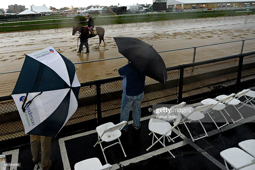 As rain falls exercise rider Willie Delgado takes Kentucky Derby winner California Chrome over the track in preparation for the 139th Preakness...