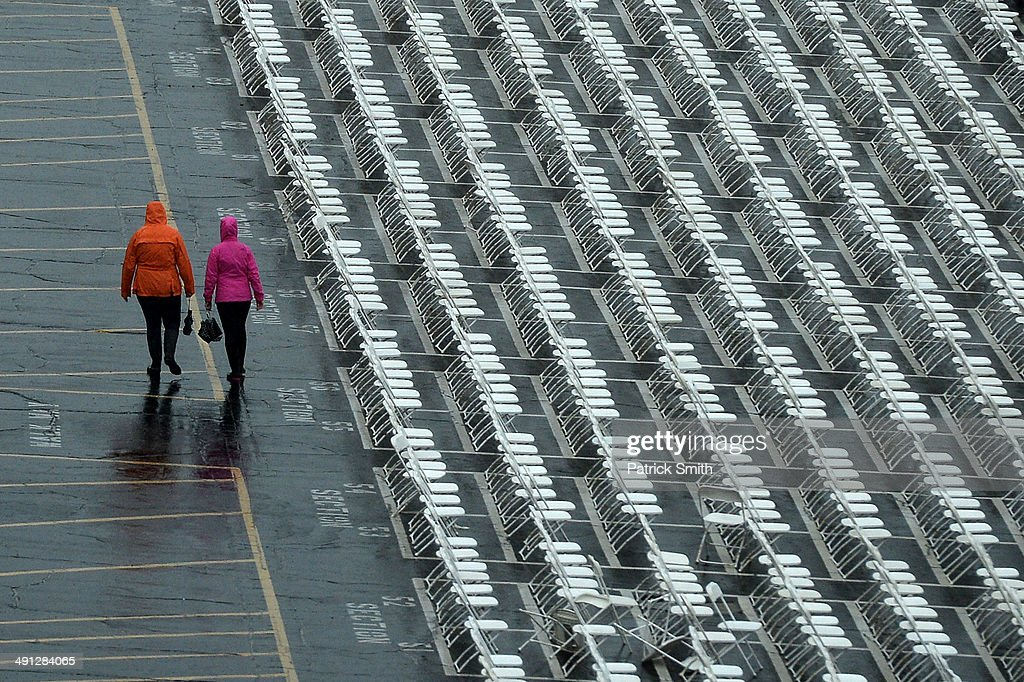 As rain falls passerby walk through the grandstand a day before the 139th Preakness Stakes at Pimlico Race Course on May 16 2014 in Baltimore Maryland