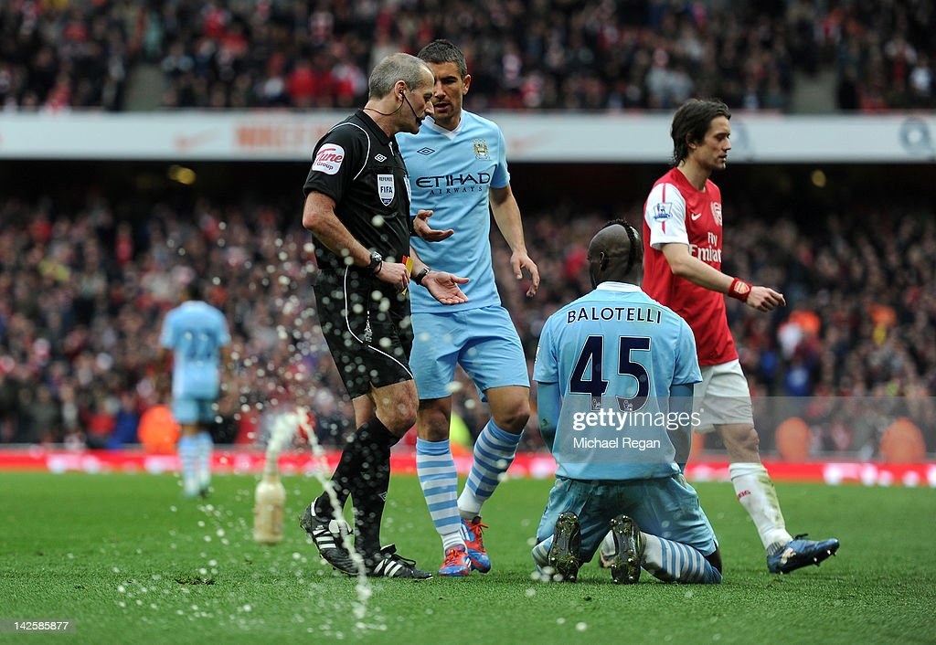 As Referee Martin Atkinson goes over to show Mario Balotelli of Man City his second yellow card a bottle of beer is thrown onto the pitch during the Barclays Premier League match between Arsenal and Manchester City at Emirates Stadium on April 8, 2012 in London, England.