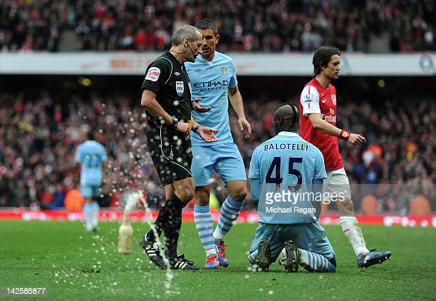 As Referee Martin Atkinson goes over to show Mario Balotelli of Man City his second yellow card a bottle of beer is thrown onto the pitch during the...