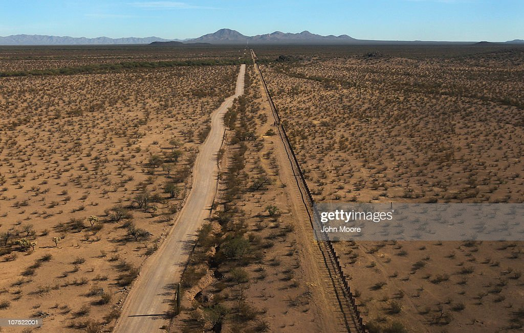 As seen from the air, the U.S.-Mexico border fence (U.S.-L) stretches through the Sonoran Desert on December 9, 2010 in the Tohono O'odham Reservation, Arizona. The remote area is a favorite spot for smugglers and illegal immigrants to cross into the United States.