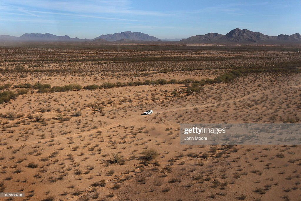 As seen from the air US Border Patrol agents follow the tire tracks of drug smugglers through the Sonoran Desert on December 9 2010 in the Tohono...