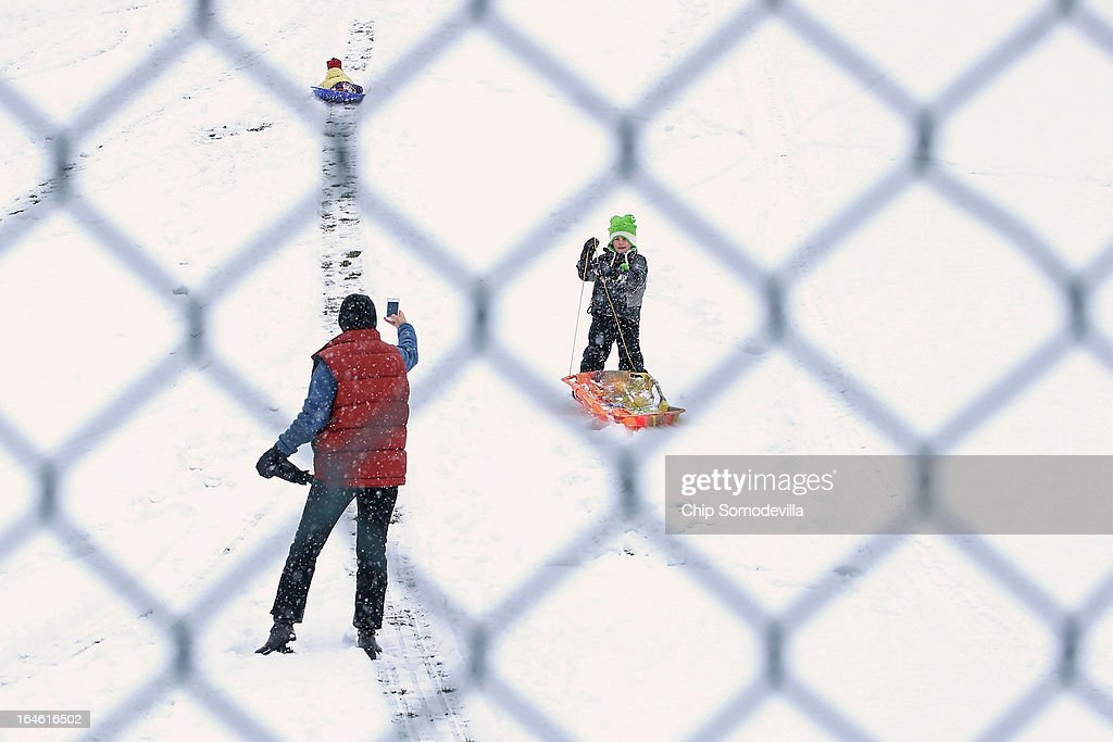 As seen through a chainlinked fence a parent takes a picture of children sledding down a snowcovered hill at Takoma Park Middle School as a wet snow...