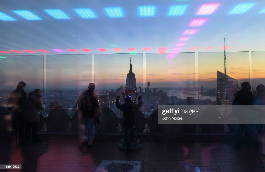 As seen through reflective glass, tourists gaze over Manhattan and the Empire State Building from an observation deck atop Rockefeller Center on February 13, 2012 in New York City. The owner of the Empire State Building, Malkin Holdings, plans to raise up to $1 billion in an initial public offering on the 102 story Manhattan landmark.