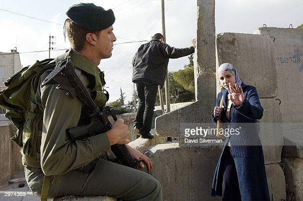 As she climbs over concrete blocks A Palestinian woman gestures her opinion of an Israeli border policeman guarding as she climbs over the concrete...