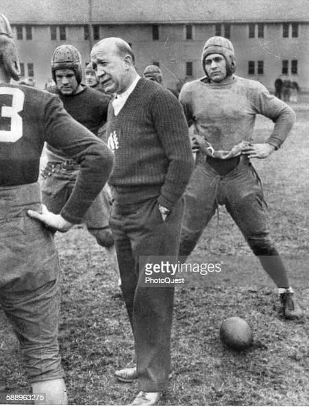 As shown in this picture with his squad Notre Dame University football coach Knute Rockne discusses fundamentals with his players South Bend Indiana...