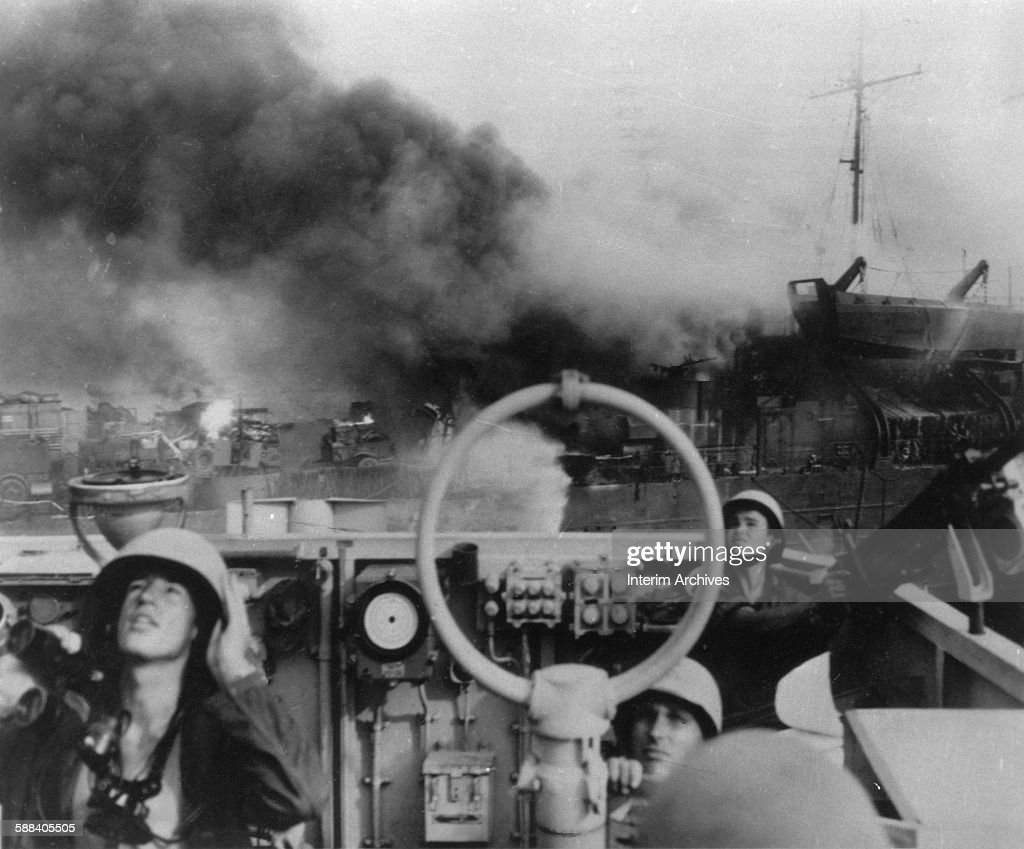 As smoke billows from a ship behind them sailors in an antiaircraft battery keep a lookout for Japanese kamikaze attacks during fighting off the...