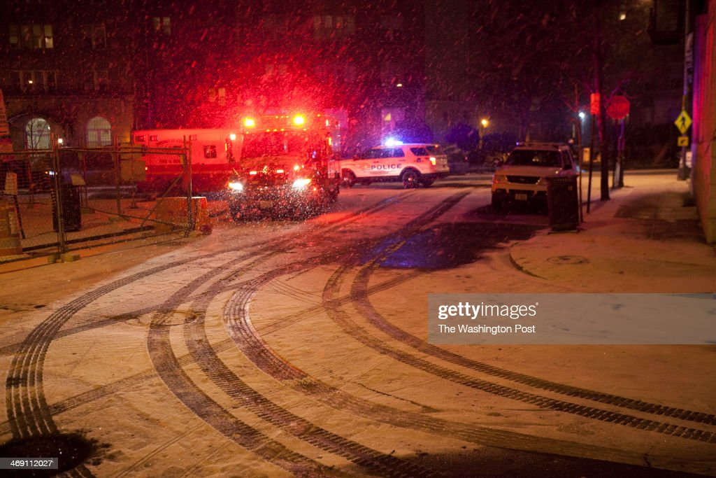 FEB 12 - WASHINGTON, DC; As snow begins to fall firefighters respond to a fire at 2518 17th street in Adams Morgan in Washington, DC on February 12, 2014. Resident Flora Zelaya was told that it might take a couple of hours before they can get back into their apartments.