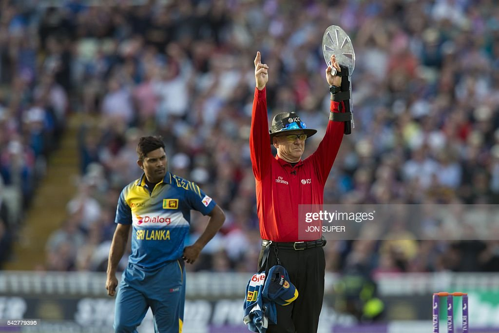 As Sri Lanaka's Seekkuge Prasanna (L) walks past umpire Bruce Oxenford signals an Alex Hales six during play in the second one day international (ODI) cricket match between England and Sri Lanka at Edgbaston cricket ground in Birmingham, central England, on June 24, 2016. England won the game by 10 wickets with more than 15 overs to spare, both Jason Roy and Alex Hales hitting unbeaten centuries. / AFP / JON