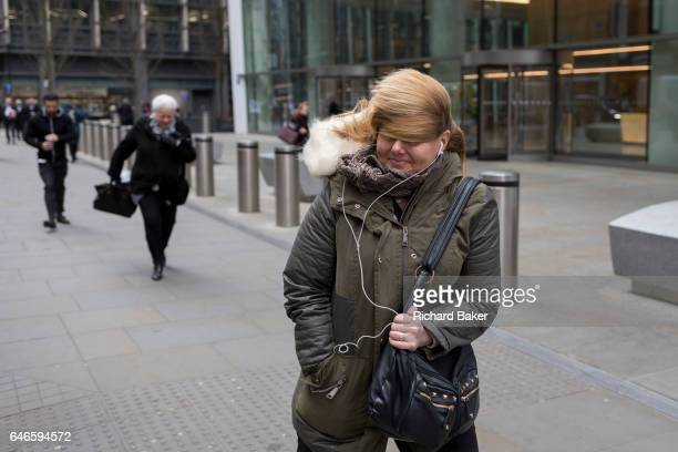 As Storm Doris blows across the UK pedestrians on Fenchurch Street brave the high winds funneled through the narrow streets squeezed between the tall...
