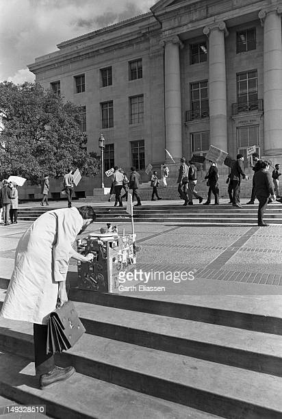 As students demontrate in the background an unidentified man in an overcoat bends down to examine an elaborately decorated box on steps in Sproul...