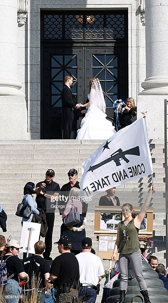 As supporters attend a gun rights rally and march, a couple has wedding pictures taken at the Utah State Capitol, on March 2, 2013 in Salt Lake City, Utah. The rally attracted several hundred people for the march to the Utah Capitol in favor of 2nd Amendment rights as gun control supporters call for more limits and bans on assault weapons.