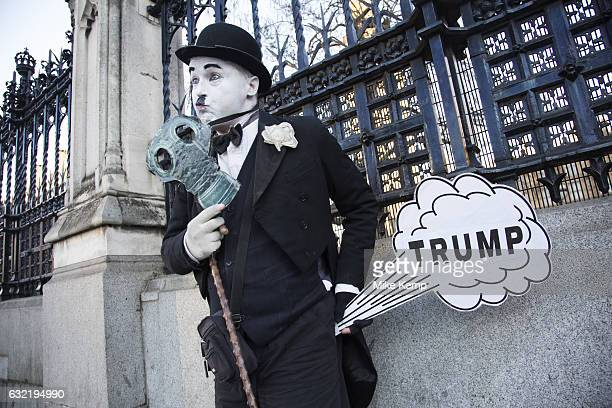 As the 45th US President is inaugurated in the USA a mime artist dressed as Charlie Chaplin stands outside Parliament with a joke 'Trump' cartoon...