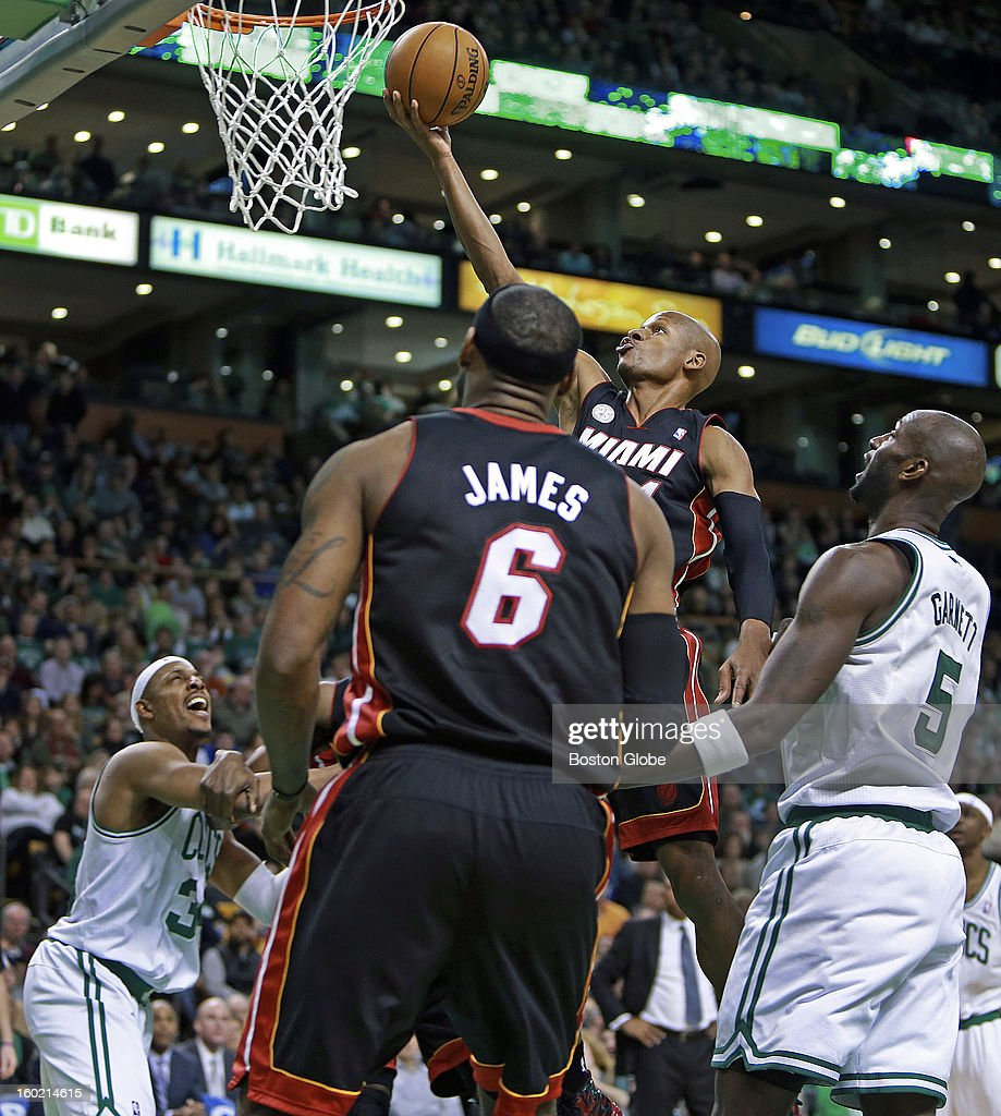 As the Celtics' Paul Pierce and Kevin Garnett can only watch as Miami's Ray Allen drives and scores two points in overtime, with teammate LeBron James (#6) also watching. The Boston Celtics hosted the Miami Heat in an NBA regular season game at the TD Garden.