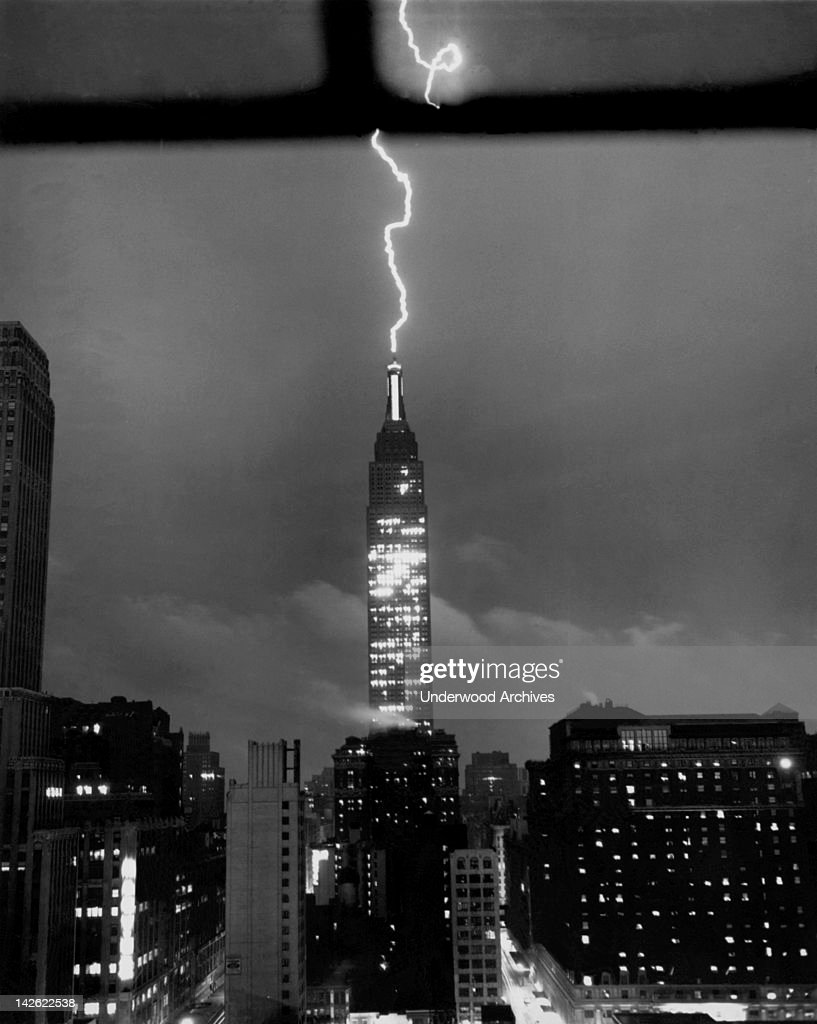 As the city is hit by a sudden summer storm, a jagged streak of lightning crackles down through the sky to roost on the tip of the dome of New York's Empire State Building high above Manhattan's streets, New York, New York, July 9, 1945.
